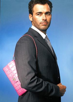 Man carrying a pink handbag.